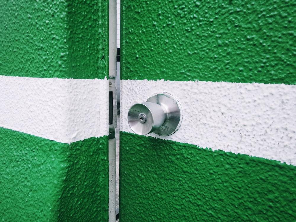 silver door knob on green and white door