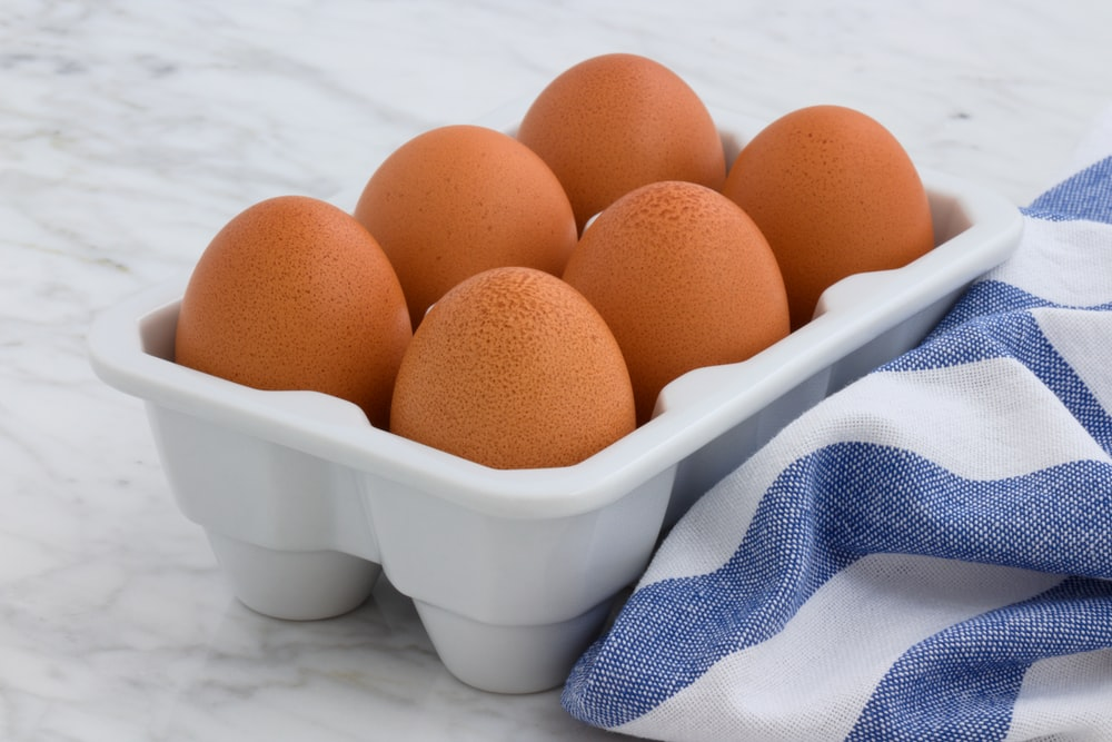 six brown eggs in white tray