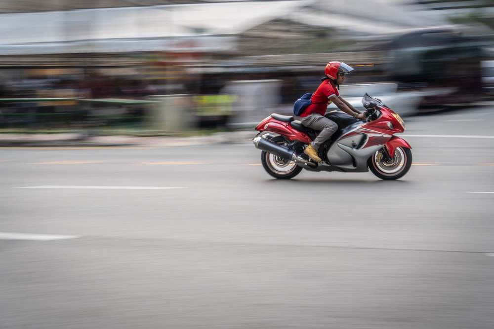 time lapse photography of person riding motorcycle on road