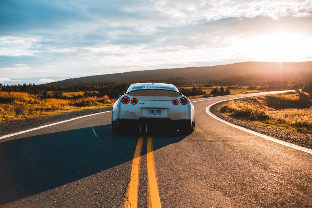 silver sports coupe on asphalt road