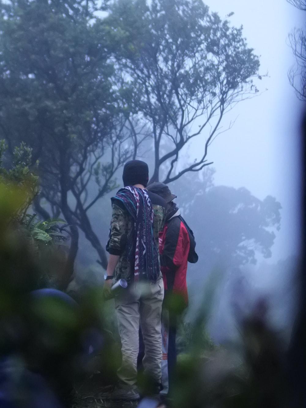 two men standing beside trees