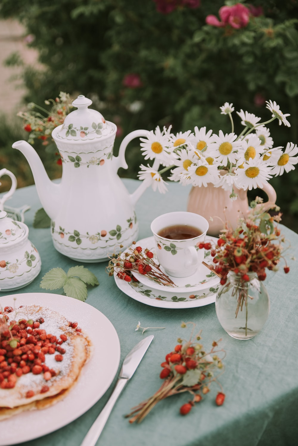 white teapot with teacup beside flowers