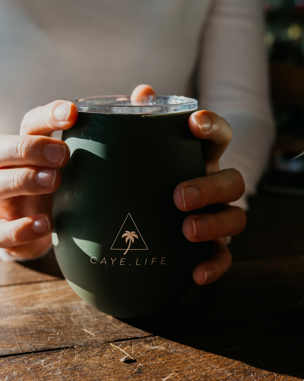 person holding black Caye Life cup