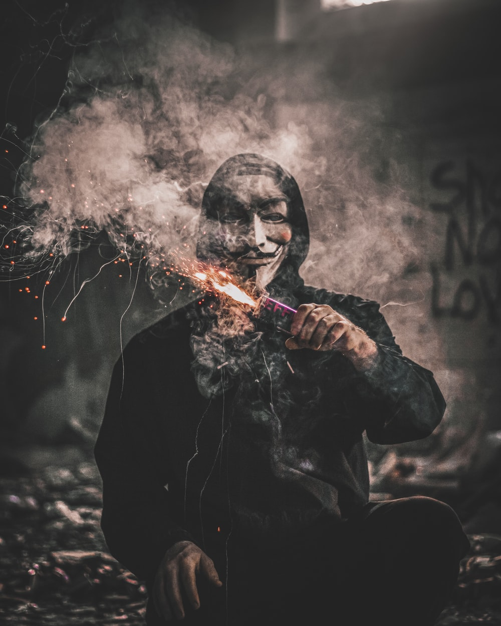 man holding sparkler wearing guy fawkes mask