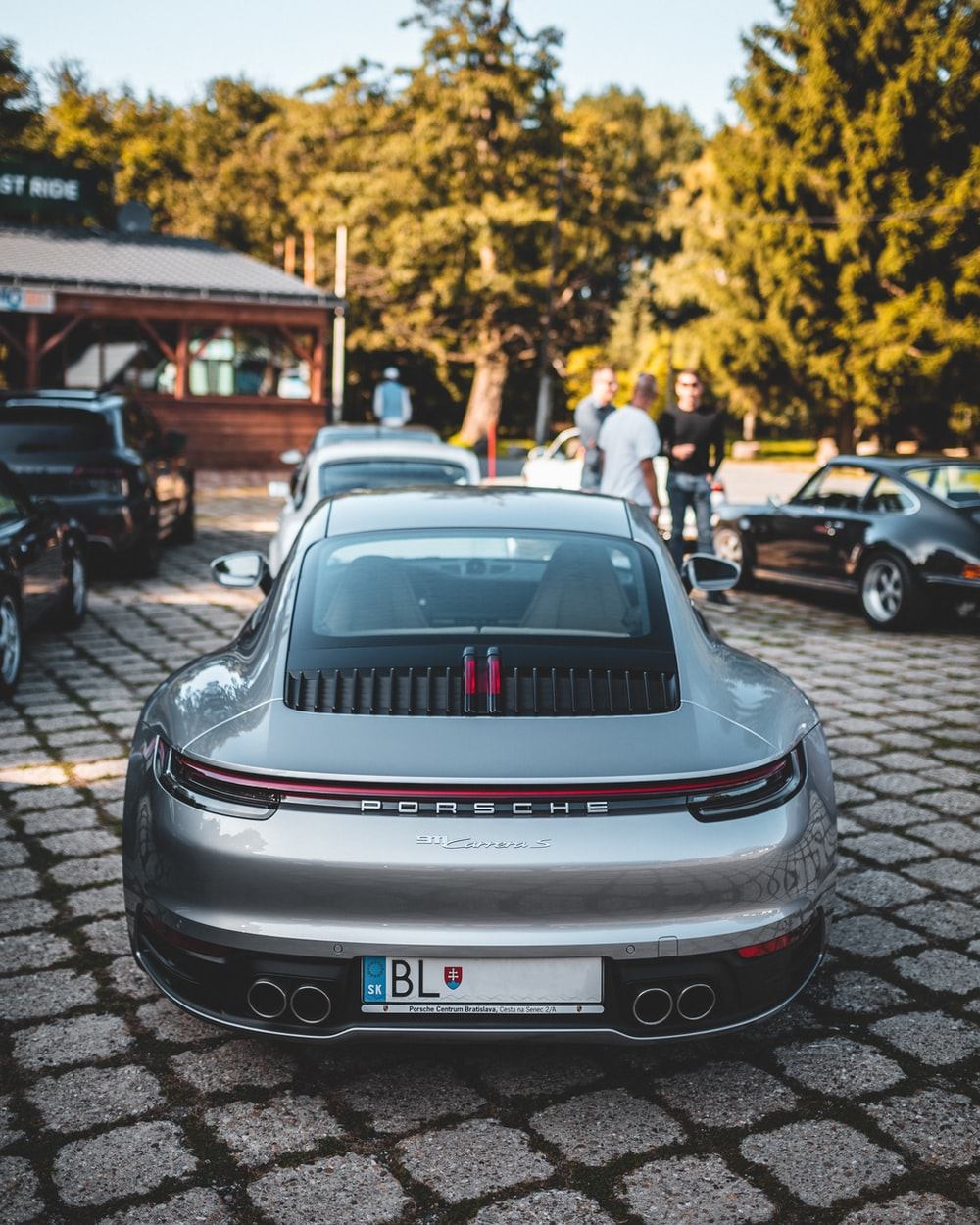 silver Porsche car parked near green trees