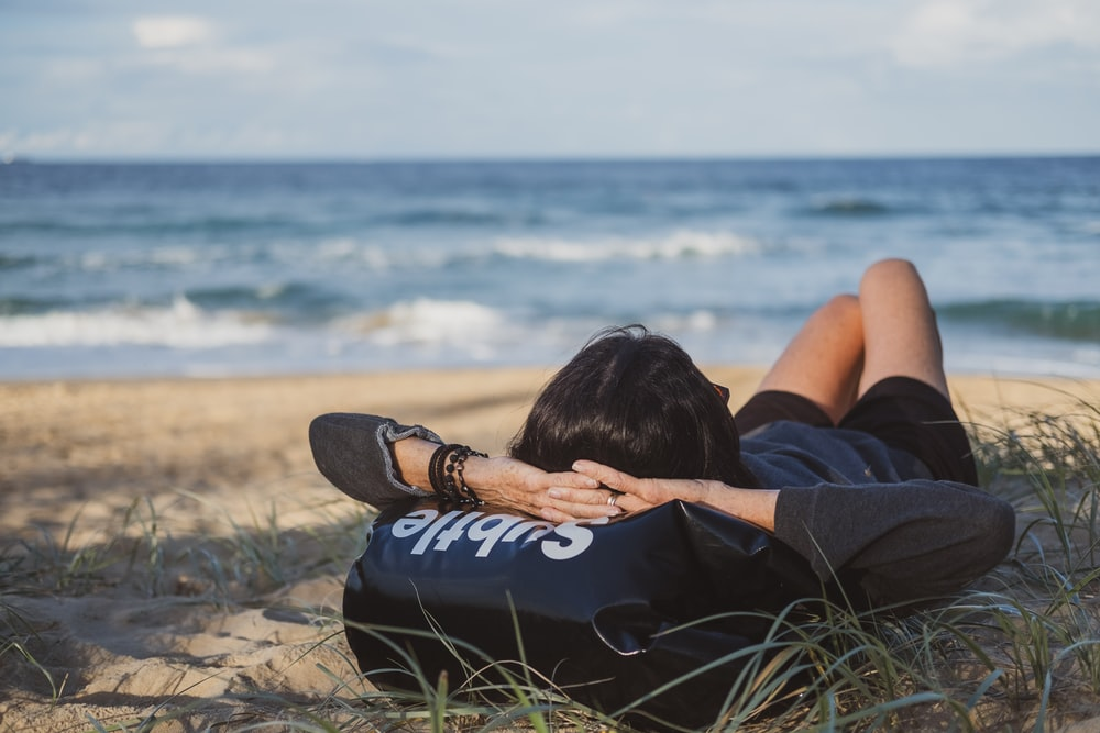 woman lying on grass front of sea at daytime