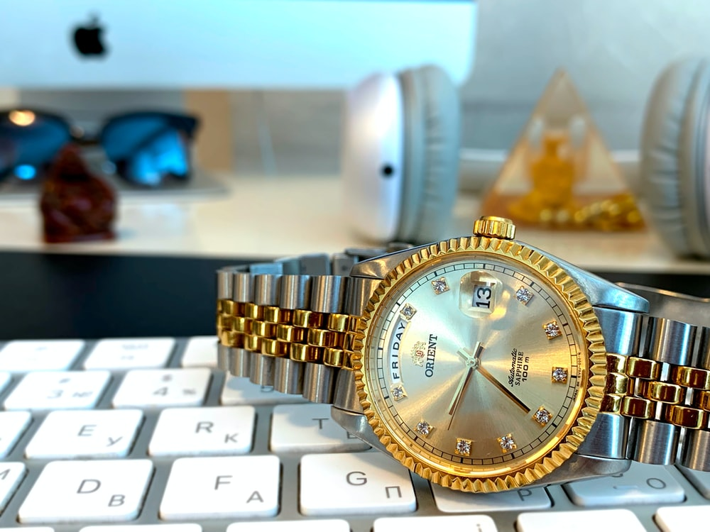 round gold-colored analog watch with band