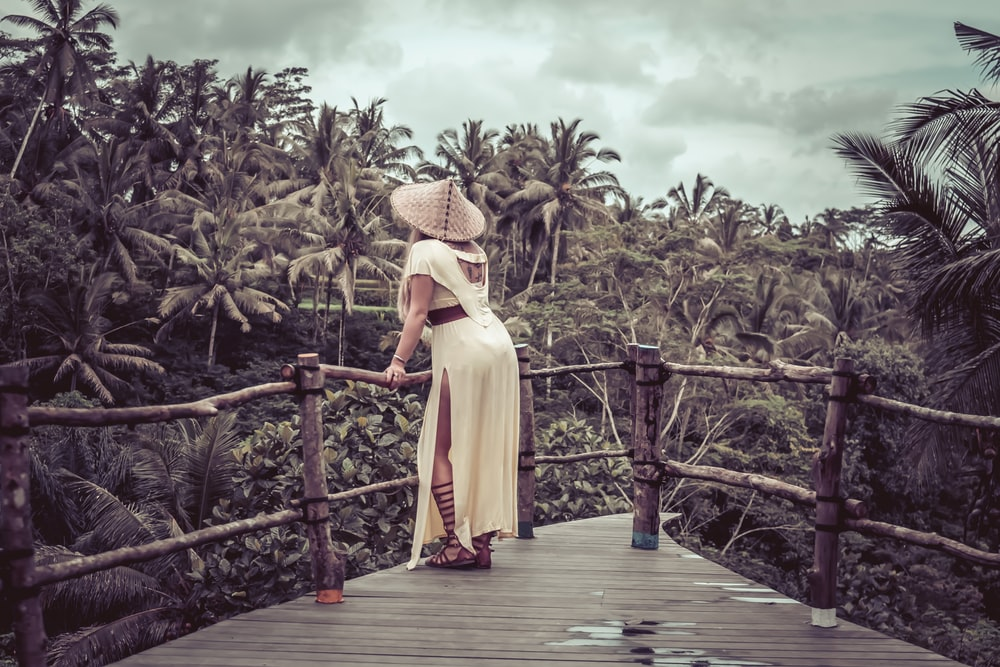 woman wears conical hat on wooden pathway