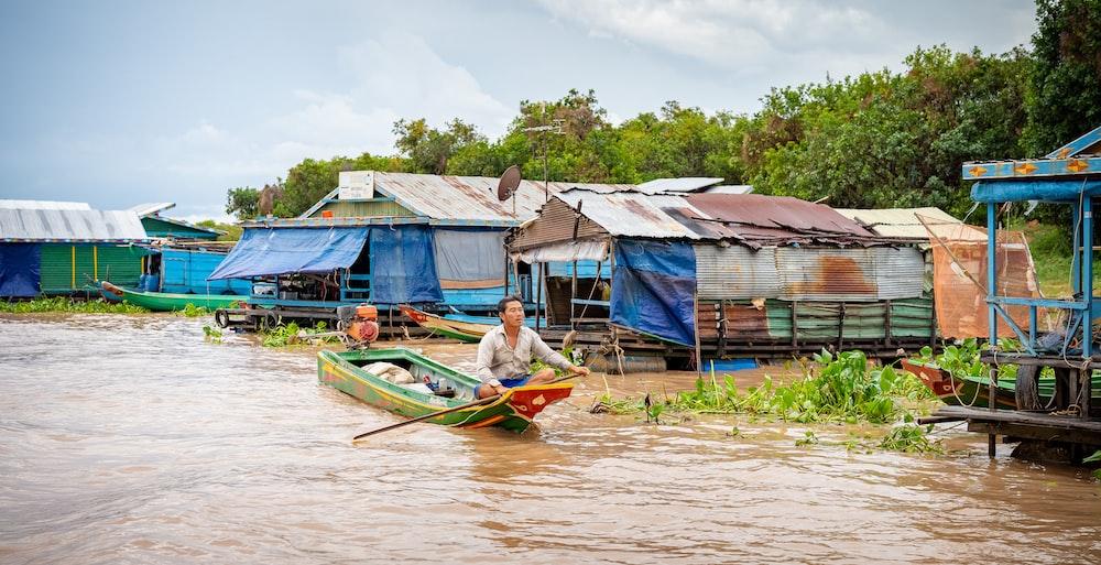 man riding boat near stilt houses