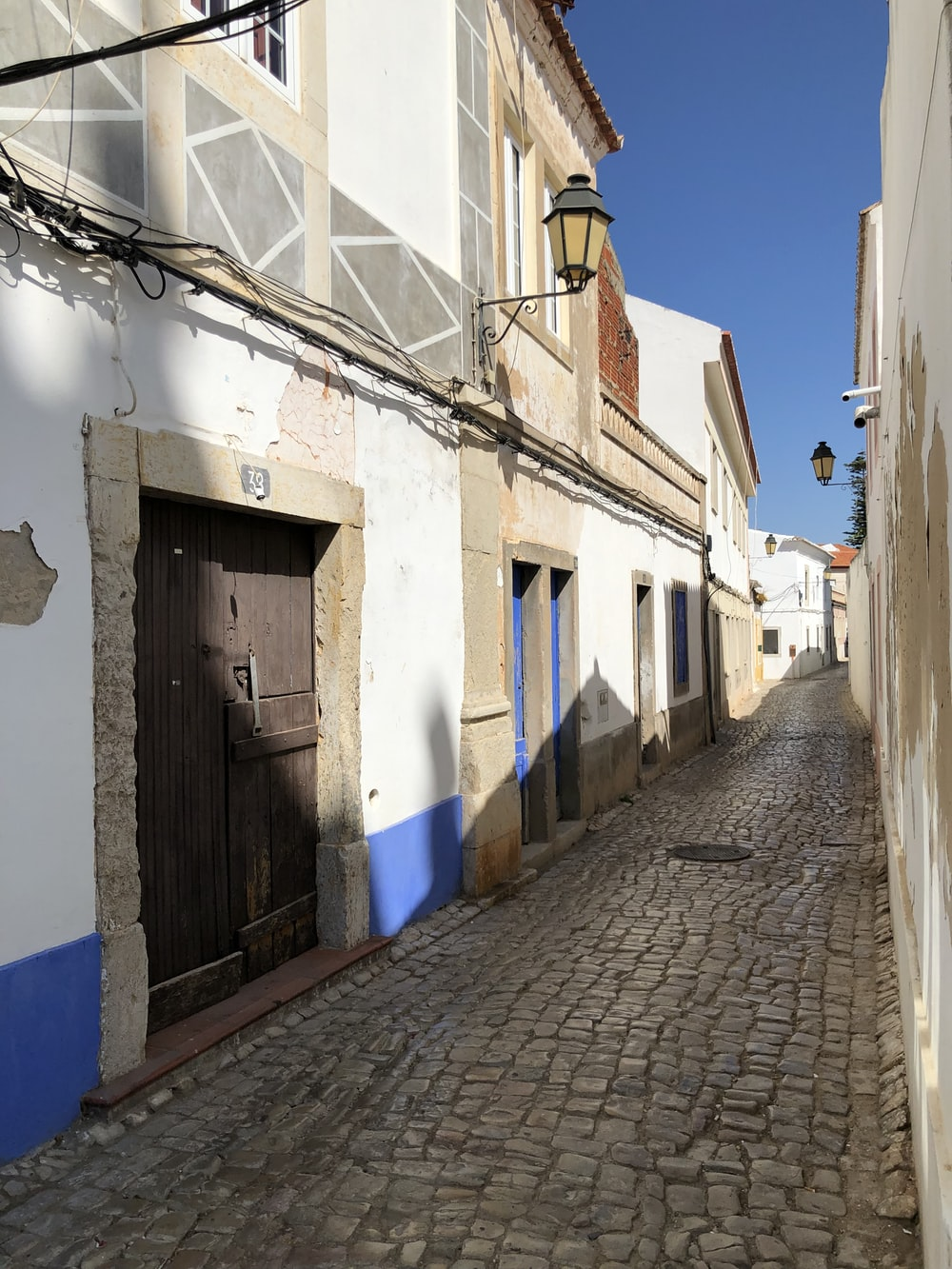 empty hallway surrounded by houses under blue sky