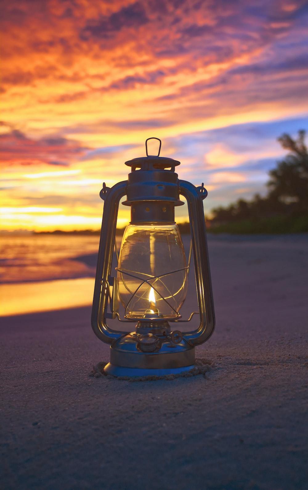 lit oil lantern on sand seashore during golden hour