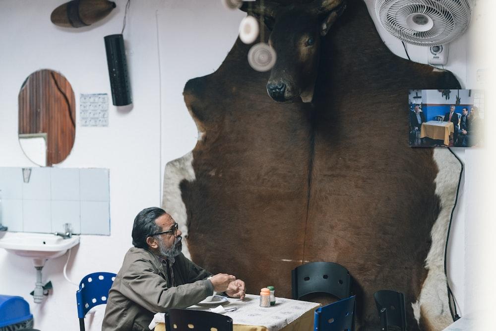 man sitting beside brown cow hide rug on wall