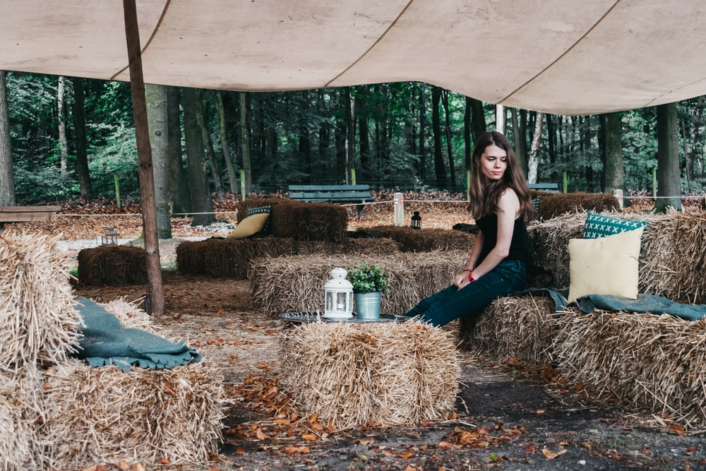 woman sitting on rolled hay at daytime