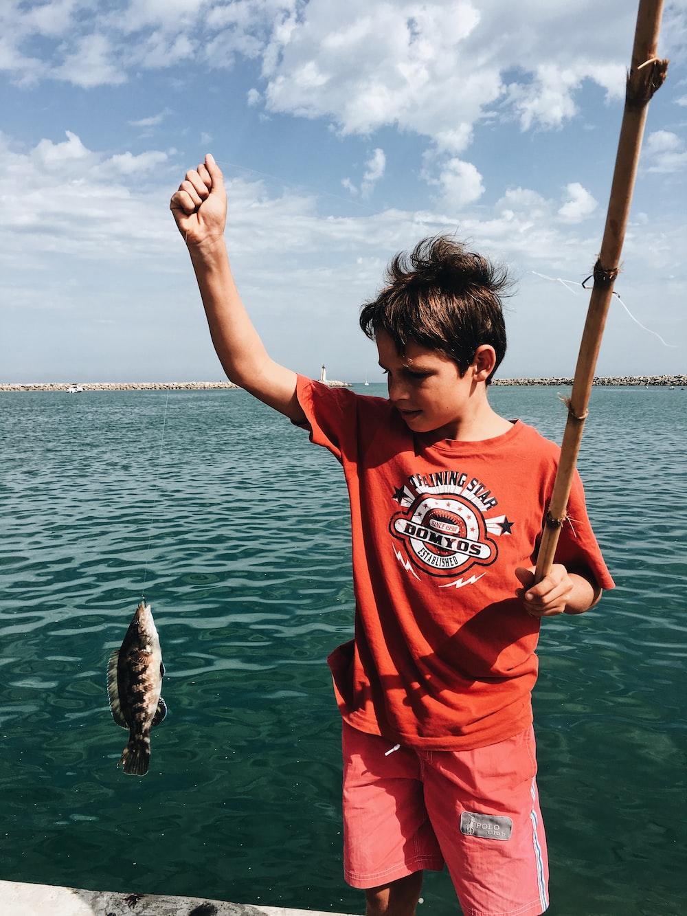 boy holds fish