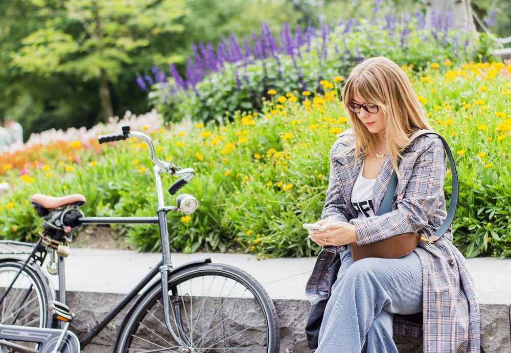 gray bicycle near to woman sitting on wall