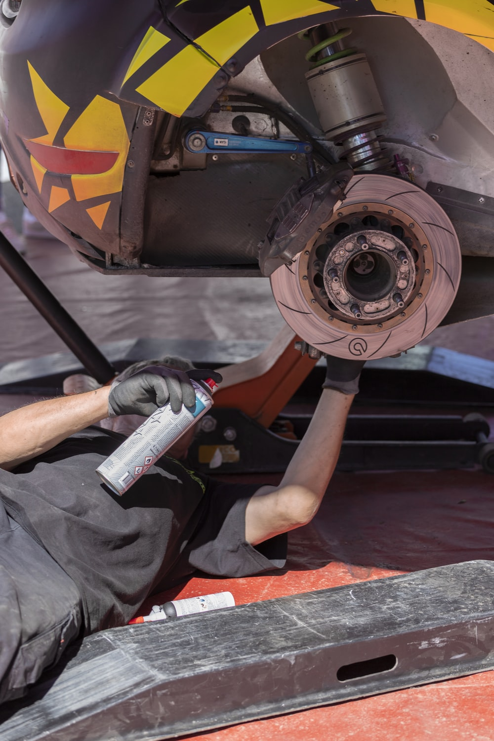 man fixing vehicle while holding spray can