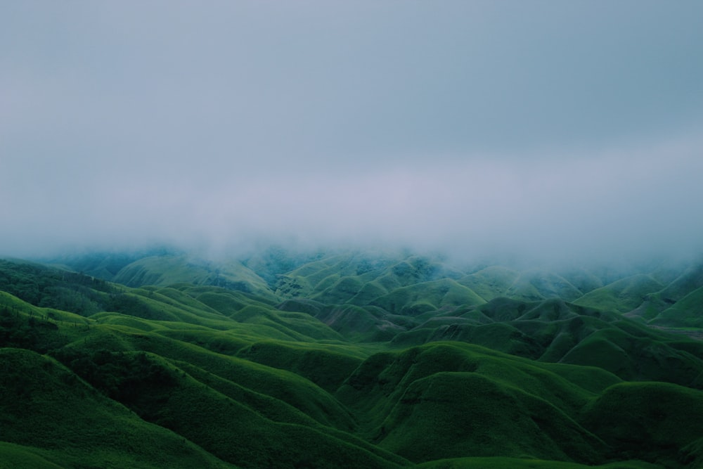green mountains under cloudy sky