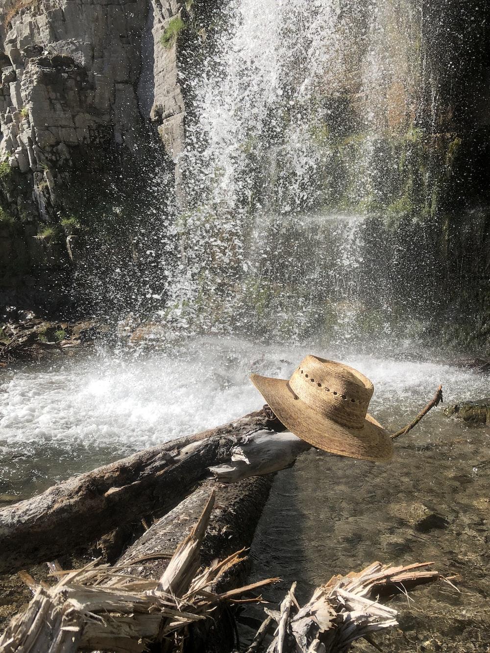 brown sun hat on edge of log near waterfalls