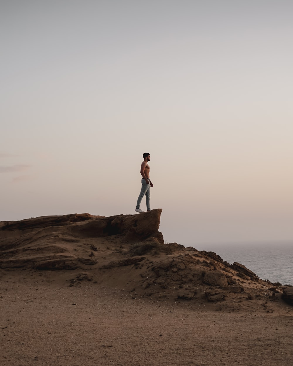 topless man standing on rocky hill