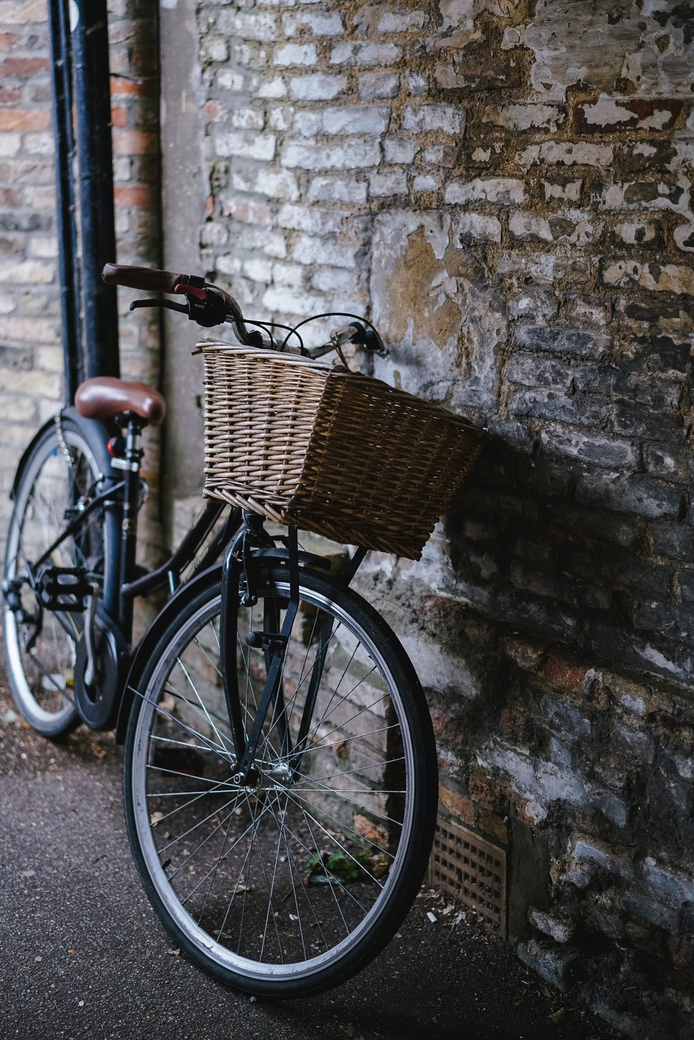black cruiser bicycle parked beside wall