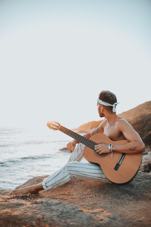 man sitting on rock near ocean