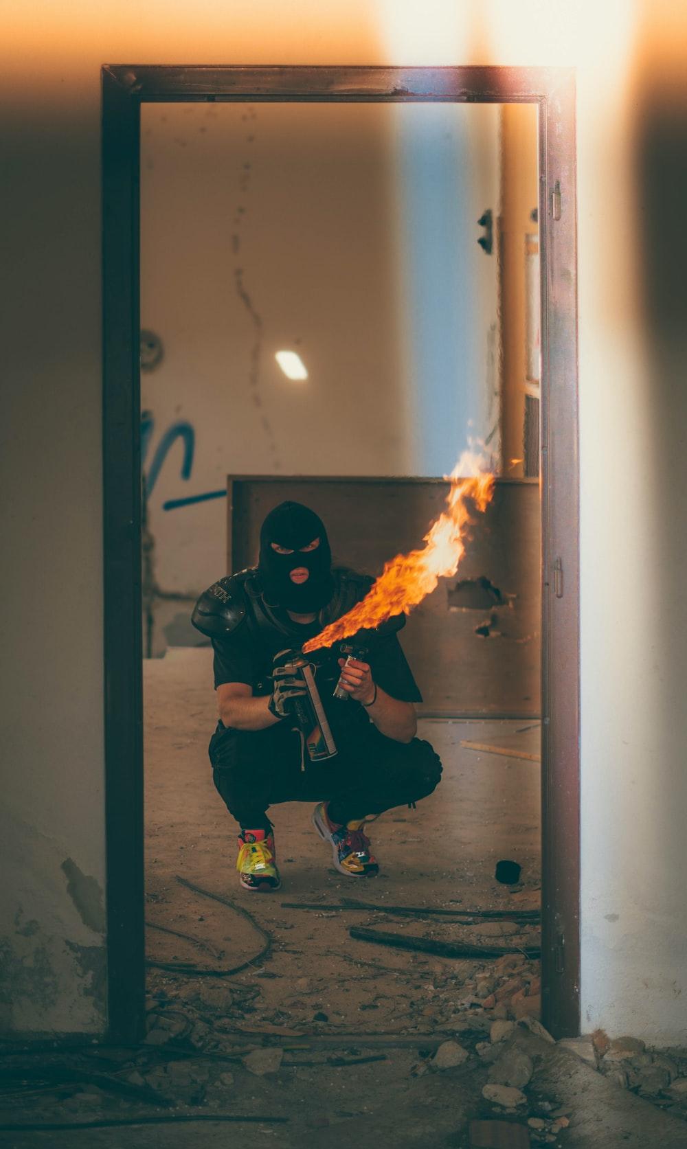 man wearing black beanie mask holding fire spray bottle