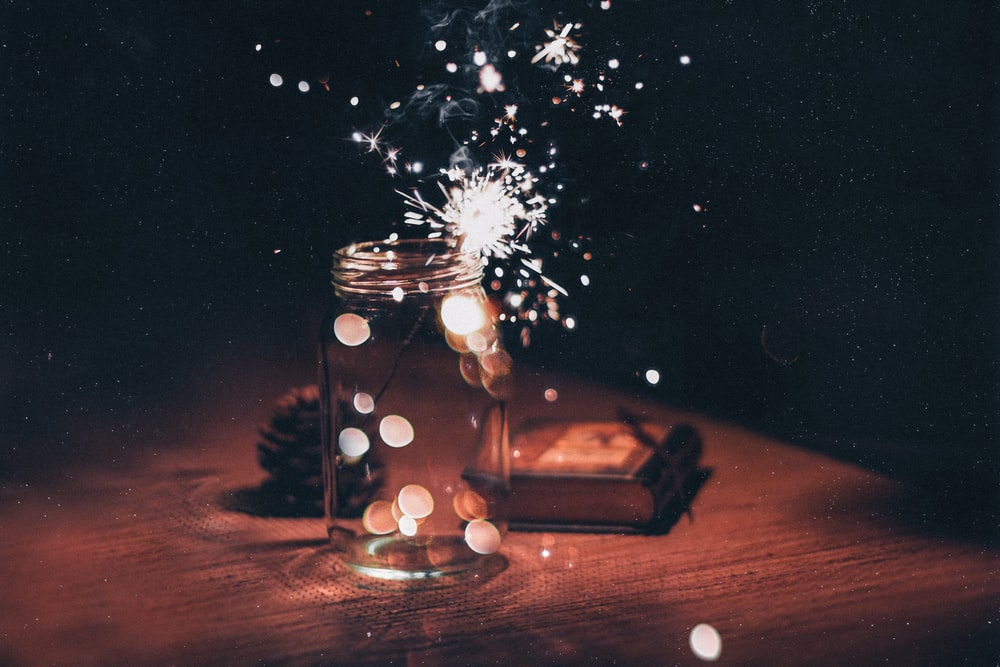 shallow focus photo of sparkler in clear glass jar