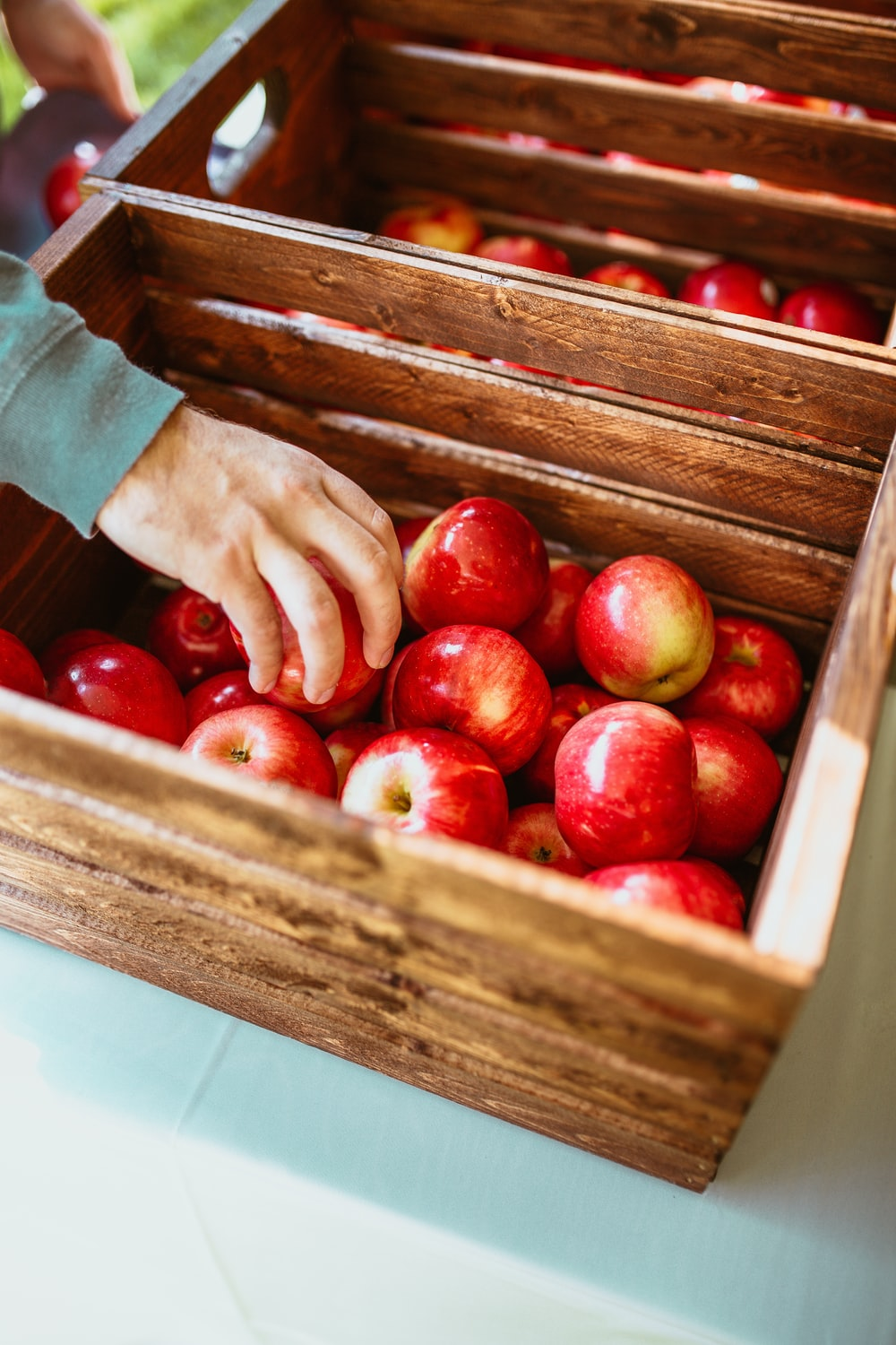 red fruits in brown wooden crate