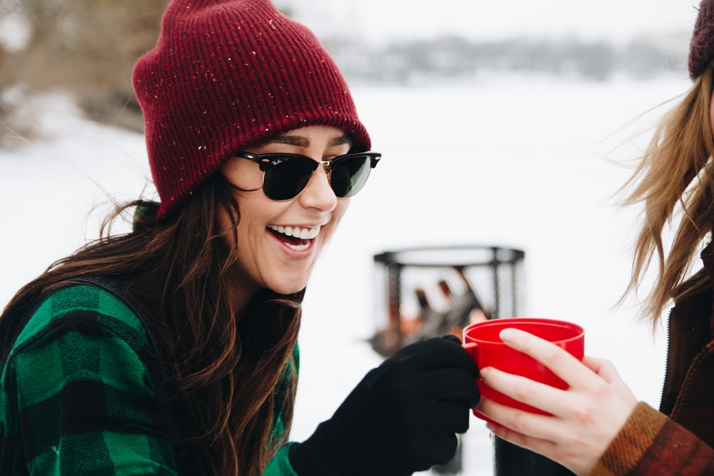 woman wearing red knitted beanie holding red plastic cup