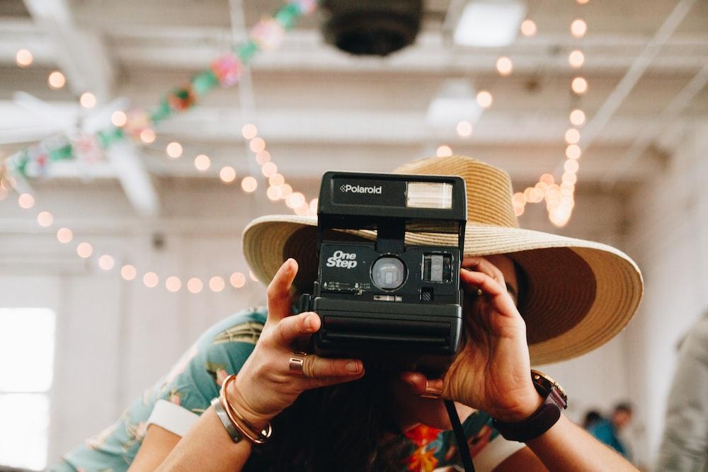 person using black Polaroid camera