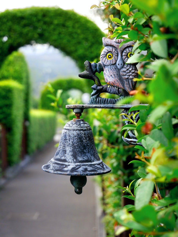 grey metal bell on hedge