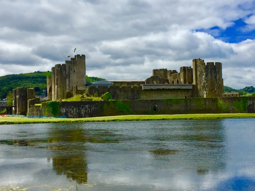ancient castle facing body of water under cloudy sky