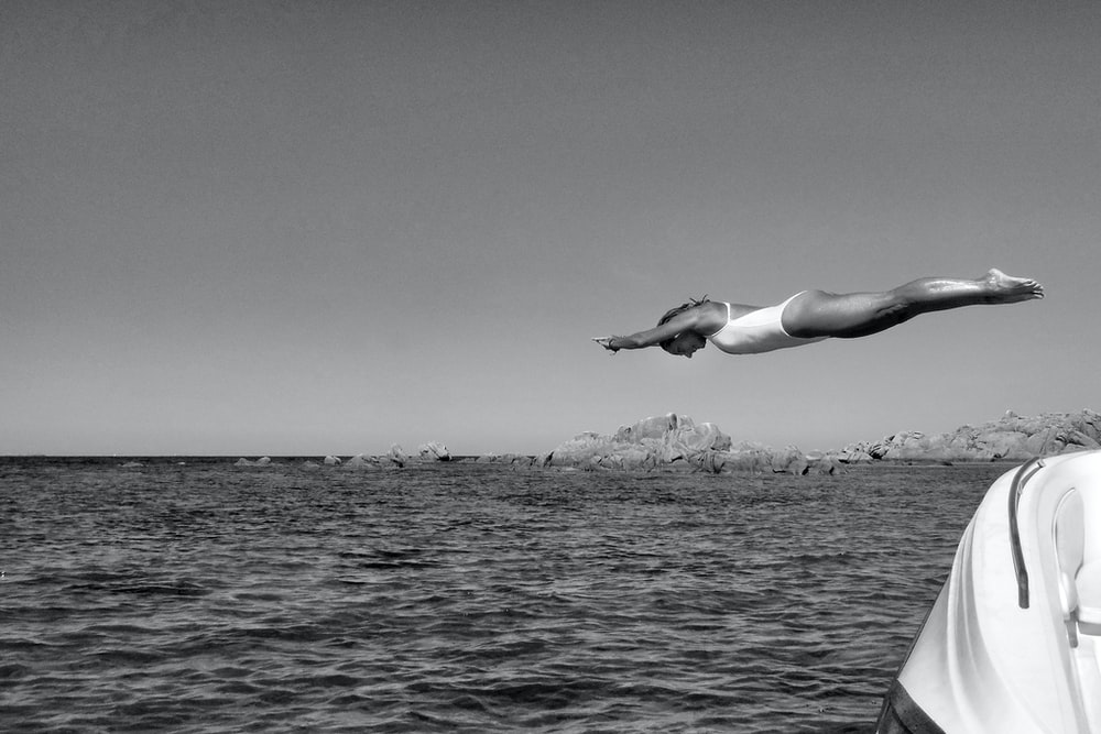 greyscale photography of woman diving on ocean