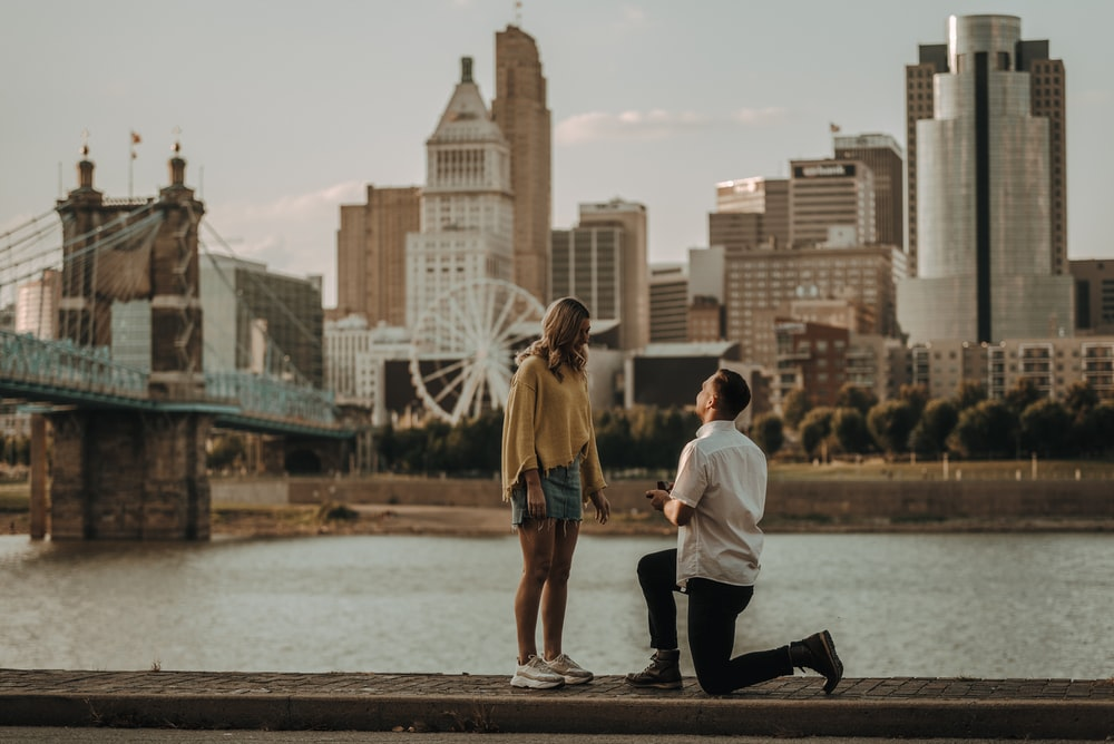 man kneeling in front of woman during daytime