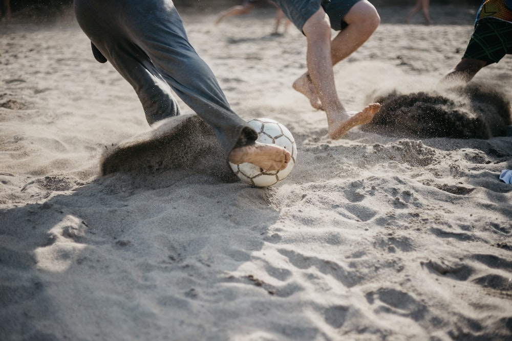 people playing soccer on sand