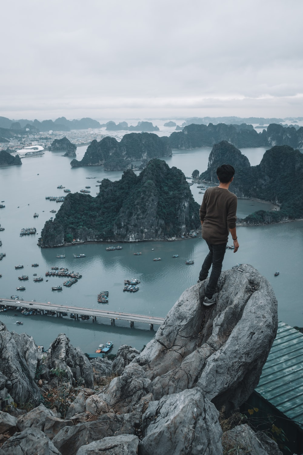man standing on top of a rocky mountain overlooking other islets