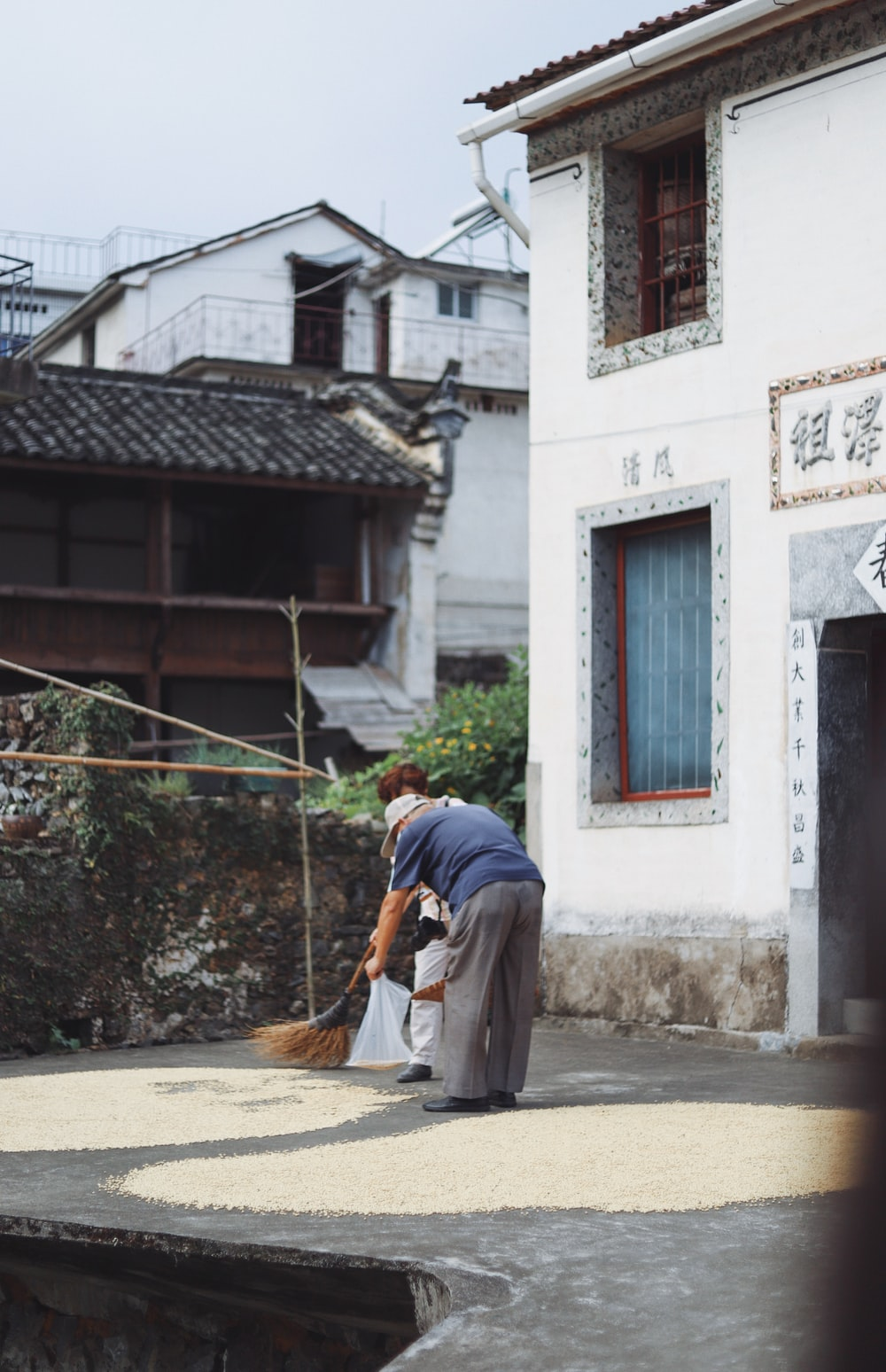 person bending beside house