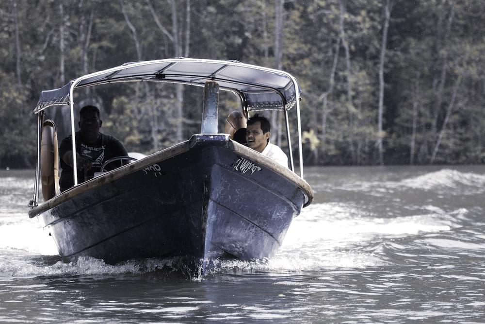 men riding gray boat during daytime