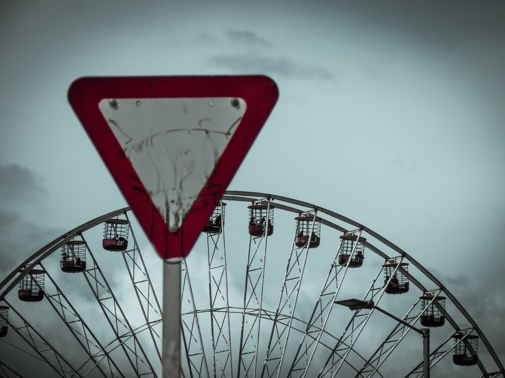red and white road sign near Ferris Wheel