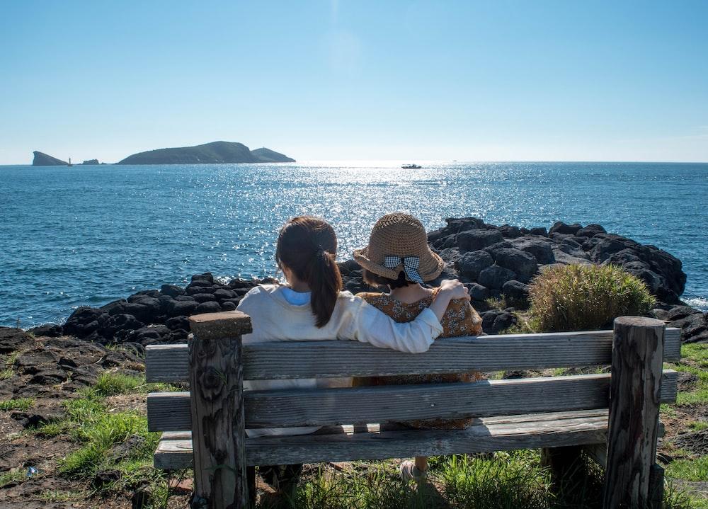 two girl sitting on bench during daytime
