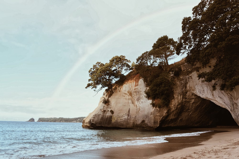 photography of mountain cliff beside seashore during daytime