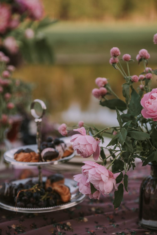 pink flowers beside 2-tier rack of pastries