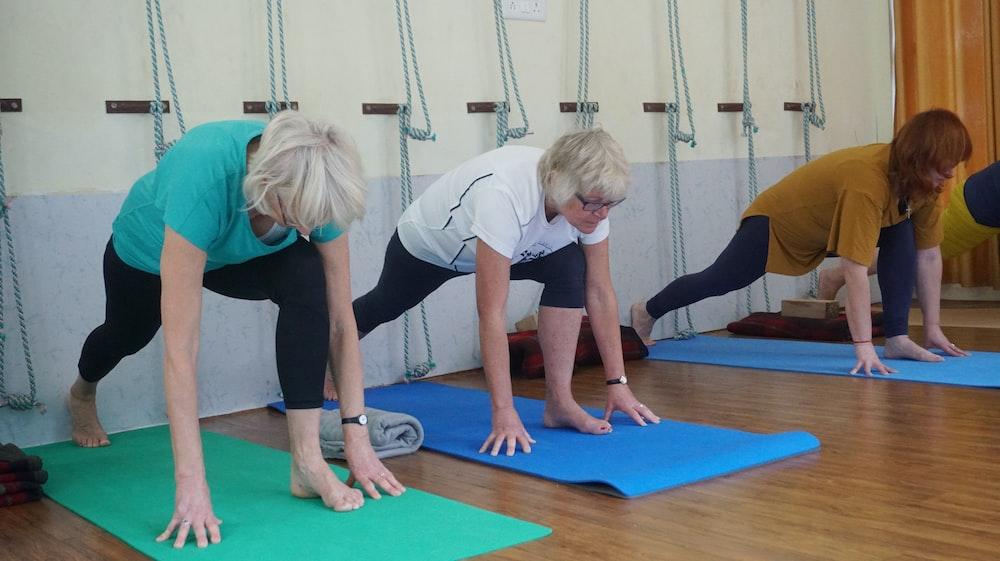 three woman doing yoga inside room