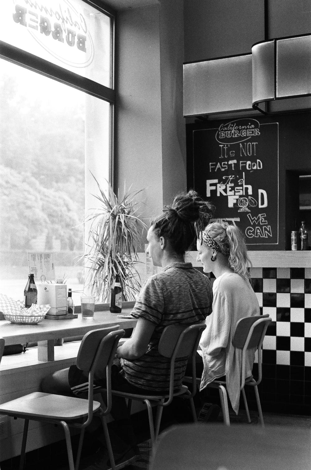 two women sitting beside table facing full-lite window inside shop