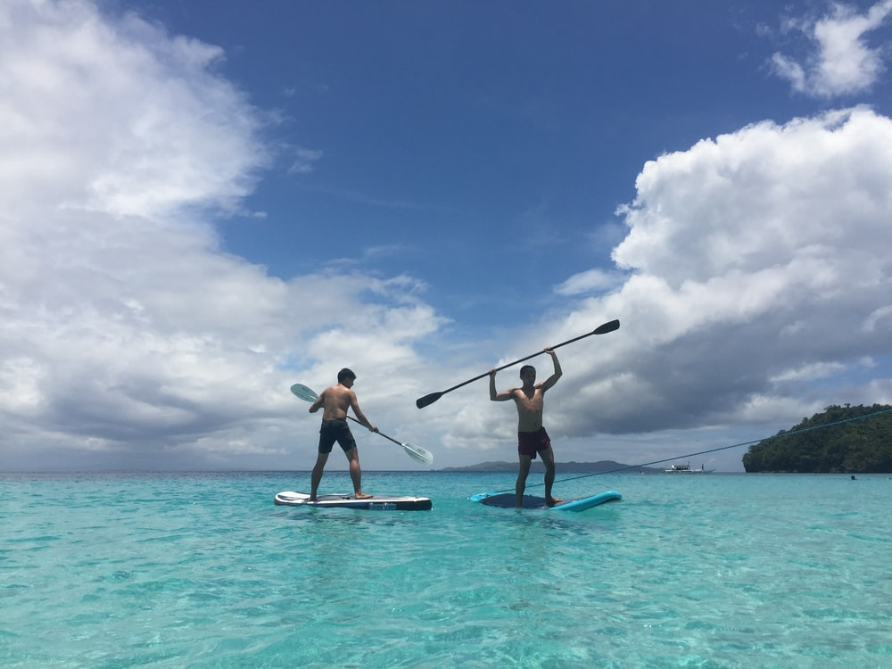two men standing on blue and white paddle boards