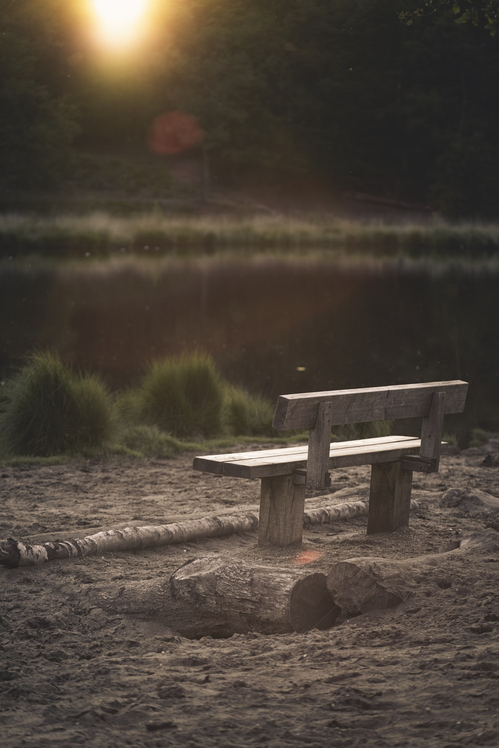 gray wooden bench front of calm water