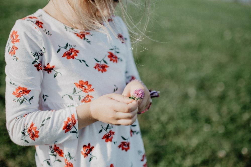 girl holds pink flower