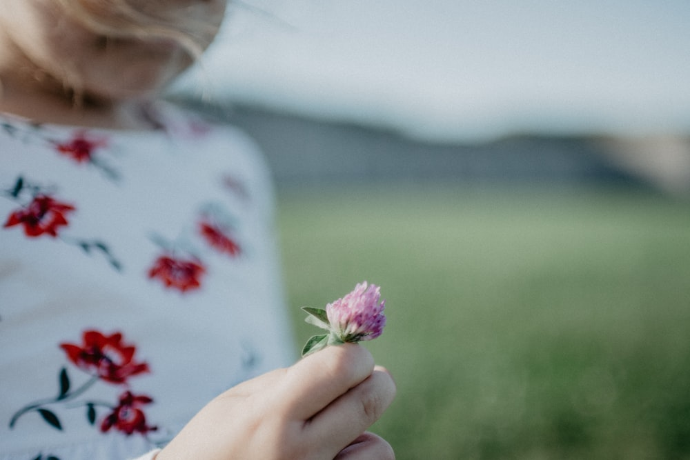 close view of girl holds pink flower