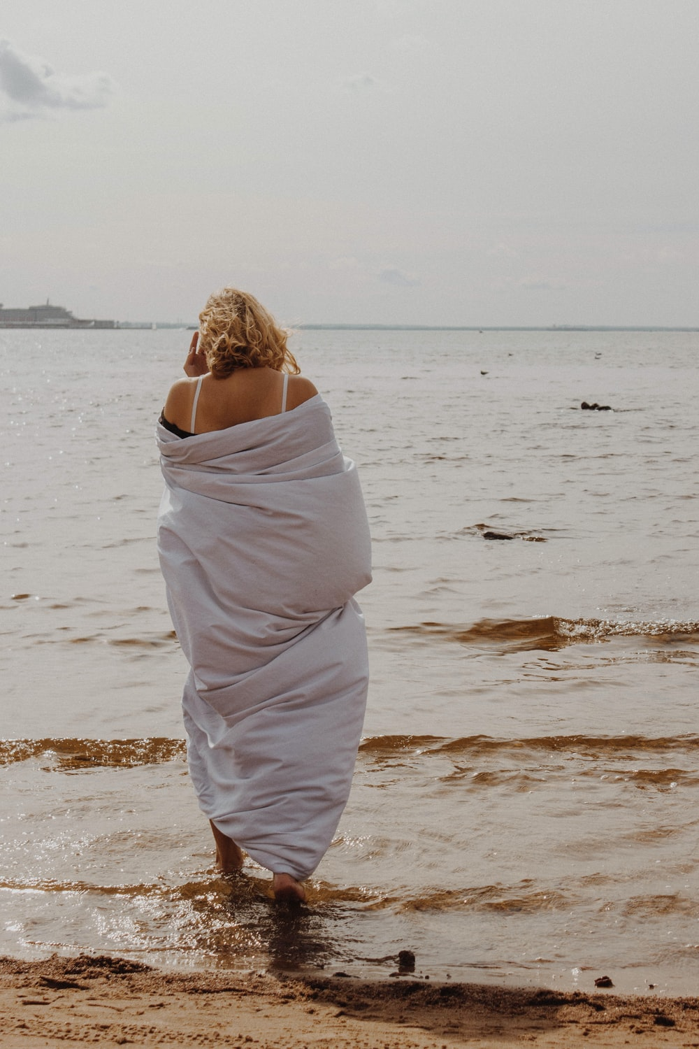 woman wrap her body with white blanket while walking at the beach
