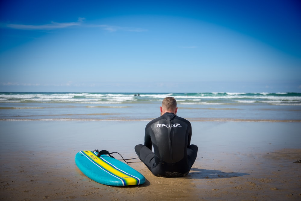 surfer sits on sand beside surfboard at the beach